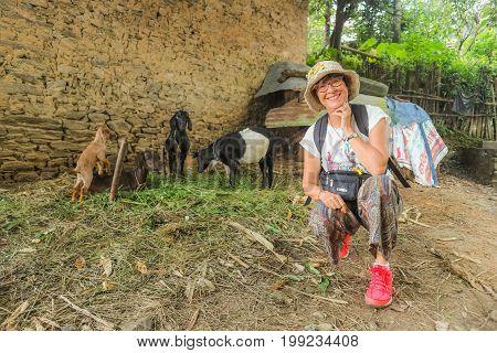 Beautiful happy woman smiling to the camera near goats in Bhutan Asia.