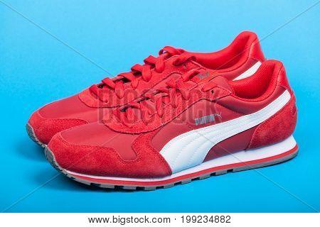 Varna Bulgaria - JUNE 17 2017. Red PUMA sport shoes on blue background. Puma a major German multinational company. Product shot