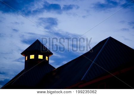 building silhouette, evening sky, roofline, cupola, dark with lighted interior