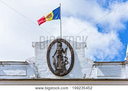 Flag and emblem of academy of science of republic of moldova office building, stefan cel mare street in the chisinau downtown, blue sky and clouds