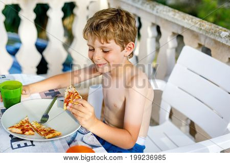 Cute healthy preschool kid boy eats fresh pizza sitting on terrace in summer, outdoors. Happy child eating unhealthy food in restaurant.