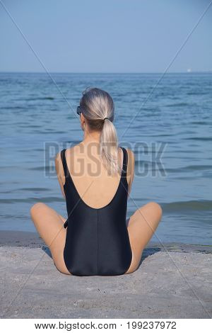 Adult woman in bathing suit sitting at the end of dock and enjoying the sea view in clear blue sky with copy space