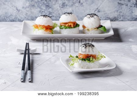 Mini rice sushi burgers with smoked salmon, green salad and sauces, black sesame served on white square plate with chopsticks over gray concrete background. Modern healthy food