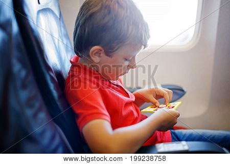Little kid boy playing tic tac toe game during flight on airplane. Child sitting inside aircraft by a window. Family going on vacation. Passenger having fun with toy.