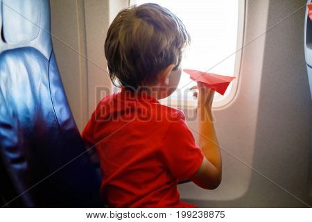 Little kid boy playing with red paper plane during flight on airplane. Child sitting inside aircraft by a window. Family going on vacation.