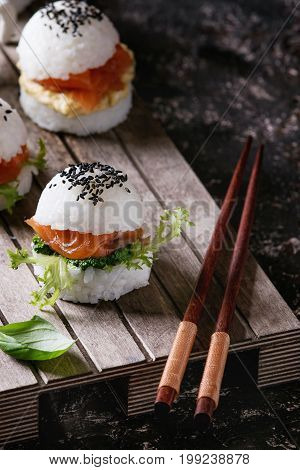Mini rice sushi burgers with smoked salmon, green salad and sauces, black sesame served on wood pallet tray with chopsticks over dark brown concrete background. Modern healthy food. Close up
