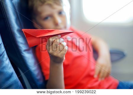 Little kid boy playing with red paper plane during flight on airplane. Child sitting inside aircraft by a window. Family going on vacation. Selective focus on toy.