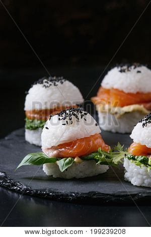 Mini rice sushi burgers with smoked salmon, green salad and sauces, black sesame served on slate stone board over black background. Modern healthy food. Close up