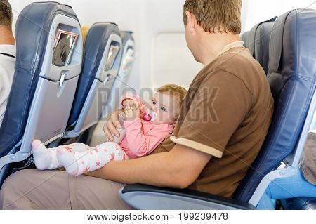 Young tired father carry his baby daughter during flight on airplane going on vacations. Baby girl drinking milk from bottle. Air travel with baby, child and family concept.