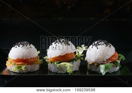 Mini rice sushi burgers with smoked salmon, green salad and sauces, black sesame served on black square plate with textile napkin over black background. Modern healthy food