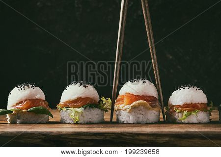 Mini rice sushi burgers with smoked salmon, green salad and sauces, black sesame served with wooden chopsticks over wood background. Modern healthy food