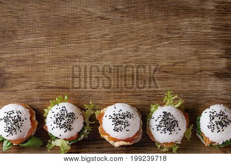 Mini rice sushi burgers with smoked salmon, green salad and sauces, black sesame served over wood background. Modern healthy food. Top view with space