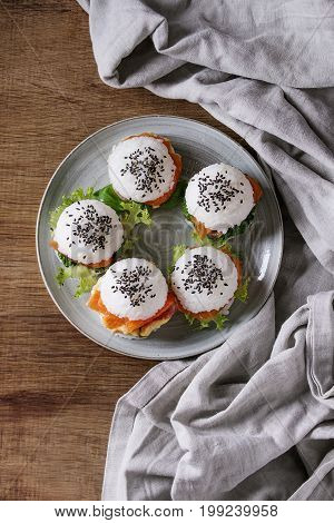 Mini rice sushi burgers with smoked salmon, green salad and sauces, black sesame served on gray plate with textile linen over wood background. Modern healthy food. Top view with space