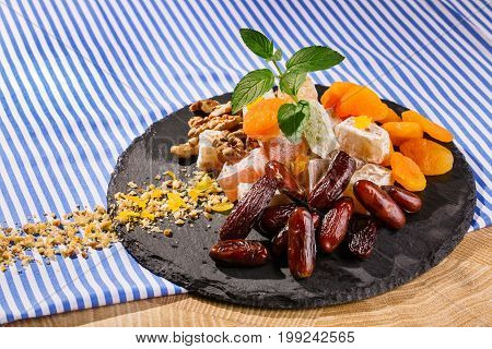Closeup of turkish delight, lokum or rahat lokum on a glass plate with date fruits, walnuts and vivid leaves of fresh mint on a striped tablecloth on a striped background.