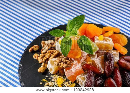 Closeup of a dark glass plate with lokum, rahat lokum or turkish delight, brown date fruits, walnuts and sappy vivid leaves of mint on a striped tablecloth on a striped background. Sweets concept.