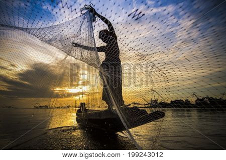 silhouette of fisherman with sunrise and big fish net in the background