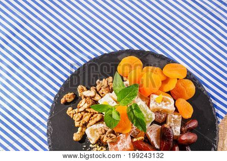Closeup of turkish delight, lokum or rahat lokum, dry apricots, sweet date fruits, walnuts, bright aromatic leaves of mint on a striped background. Top view of sweets.