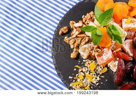 Top view of dry apricots, turkish delight, rahat lokum, sweet date fruits, walnuts, bright aromatic leaves of mint in a plate and on a striped background.