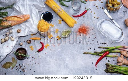 A top view of a great variety of pasta on a gray stone background. A bright set of ginger, olives, tableware, quail eggs, baguette, spices, asparagus, yellow bell pepper, red hot chili pepper.