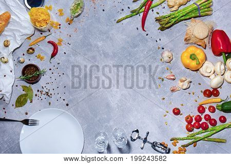 A view from above on a beautiful composition. A plate with a cutlery next to different bright raw vegetables. Asparagus, bell pepper, mushrooms, garlic and chili pepper on a gray stone background.
