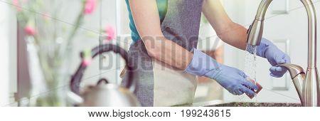 Lady Wetting Sponge Over Sink