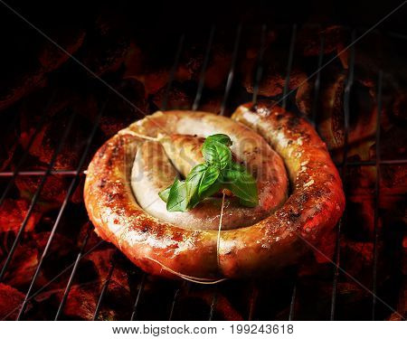 cumberland sausage, spiral pork sausage on bbq grill with flame, homemade