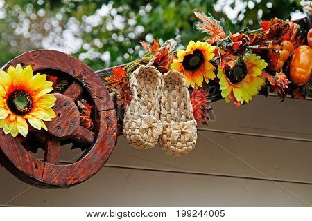 Bast shoes sunflowers and wheel as autumn decoration for street festival