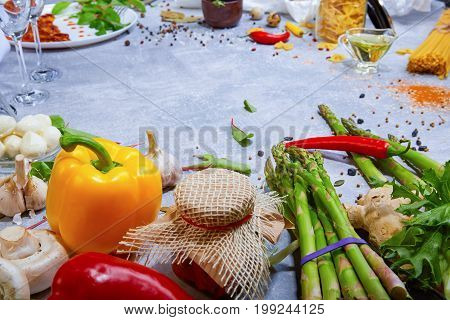 A close-up picture of yellow and red bell peppers, mushrooms, asparagus, garlic, pickles, potatoes, pasta, ginger next to tableware. Fresh ingredients for healthy dinner dishes on a table background.