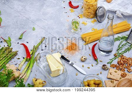 A top view of a water bottle next to pasta variety and a glass container for butter on a gray stone background. Olive oil, butter knife, vegetables, olives, herbs, nuts and spices. Cooking concept.