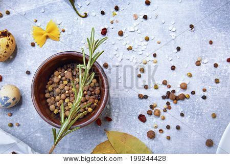 A view from above on fragrant seasoning. Flavoring on a gray stone background. A wooden bowl full of colorful spices next to bay leaves and quail eggs. Flavoring for taste. Copy space.