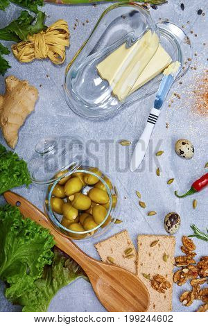A view from above on supper ingredients. Olives, butter, salad leaves, bread, walnuts, ginger, red hot chili pepper, pasta, quail eggs, spices and tableware Food preparation
