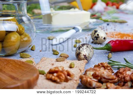 Macro picture of supper ingredients. Olives, butter, salad leaves, bread, walnuts, ginger, red hot chili pepper, pasta, quail eggs spices and tableware Food preparation