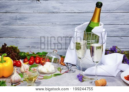 A close-up picture of a champagne bottle and glasses on a gray wooden background. Cherry tomatoes, yellow bell pepper, garlic, salad leaves, peeled potatoes and olive oil next to purple dried flowers.