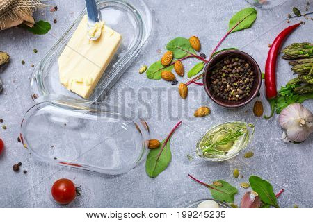 A top view of a glass container for butter, a wooden bowl for seasoning, metal butter knife, almond nuts, olive oil with rosemary, tomato, garlic, red hot chili pepper and salad leaves. Food concept.
