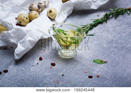 Convenience food on a grease-proof paper. Beautiful little quail eggs next to an oil tank and a rosemary twig. Food ingredients on a gray stone table background. Copy space.