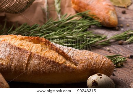 A close-up picture of a bright brown, crunchy and soft bread on an old table background. A fantastic baguette with spices and little quail egg. Nutritious rustic breakfast concept.