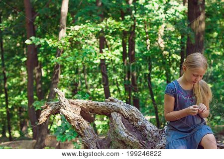 Girl sitting on a tree stump in a forest