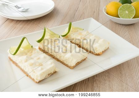 Key Lime pie slices arranged on a white serving platter with plates cake forks lemons and limes in the background. Selective focus shallow depth of field.