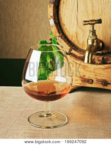 Cognac Barrel And Glass Of Brandy On Table. Winemaking Product