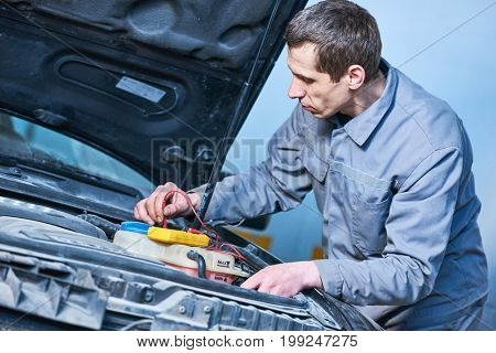 auto electrician mechanic at work with car