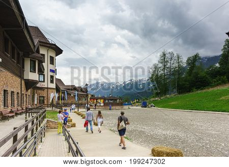 Tourists Walking Near The Building Of The Rosa Shelter With A Restaurant Den Ski Resort