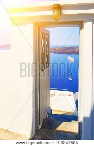 open door to terrace with table and chair and beautiful view of sea and mountains in Oia, on Santorini island