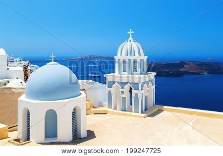 two blue domes of the beautiful Church of Fira, Santorini in the background of Caldera and the sea