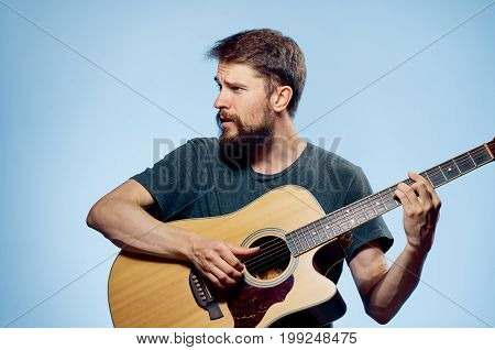Man with a beard on a blue background playing the guitar, emotions, musical instruments.
