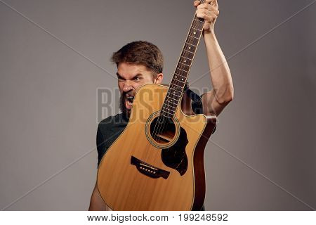a man with a beard on a gray background holding a guitar, scream, emotion.