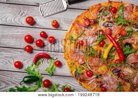 Top view of a metal scapula for a hot, spicy pizza with fat ham, grilled cheese, healthy tomatoes and arugula on a gray rustic background. Fresh and beautiful pizza for restaurants and gourmets.