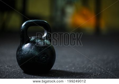 A close-up picture of metal black kettlebell used perform ballistic exercices. Sports equipment on a blurred background. Kettlebell on a gym ground. Sports, health, gym, workout concept.