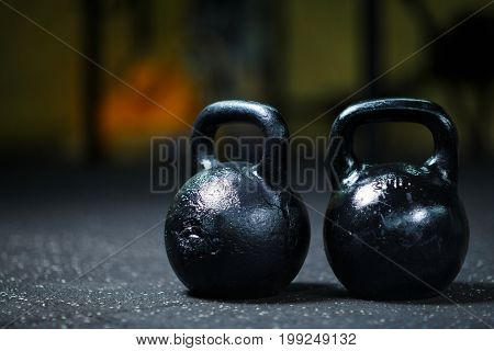 A close-up picture of two metal black kettlebells used perform ballistic exercices. Sports equipment on a blurred background. Kettlebell on a gym ground. Sports, health concept