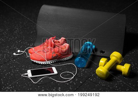 A colorful set of sportive accessories for gym training on a black background. Blue sportive bottle, bright orange training shoes, yellow dumb-bells, black pilates mat. Sports, training concept.