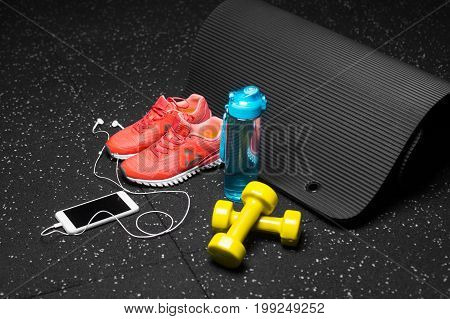 A colorful composition of sportive accessories for gym training on a black background. Blue sportive bottle, bright orange training shoes, yellow dumb-bells, black pilates mat. Sports concept.